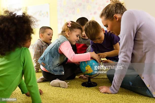Kuriositäten Kinder untersuchen Welt Globus mit Ihrem Lehrer im Vorschulalter.