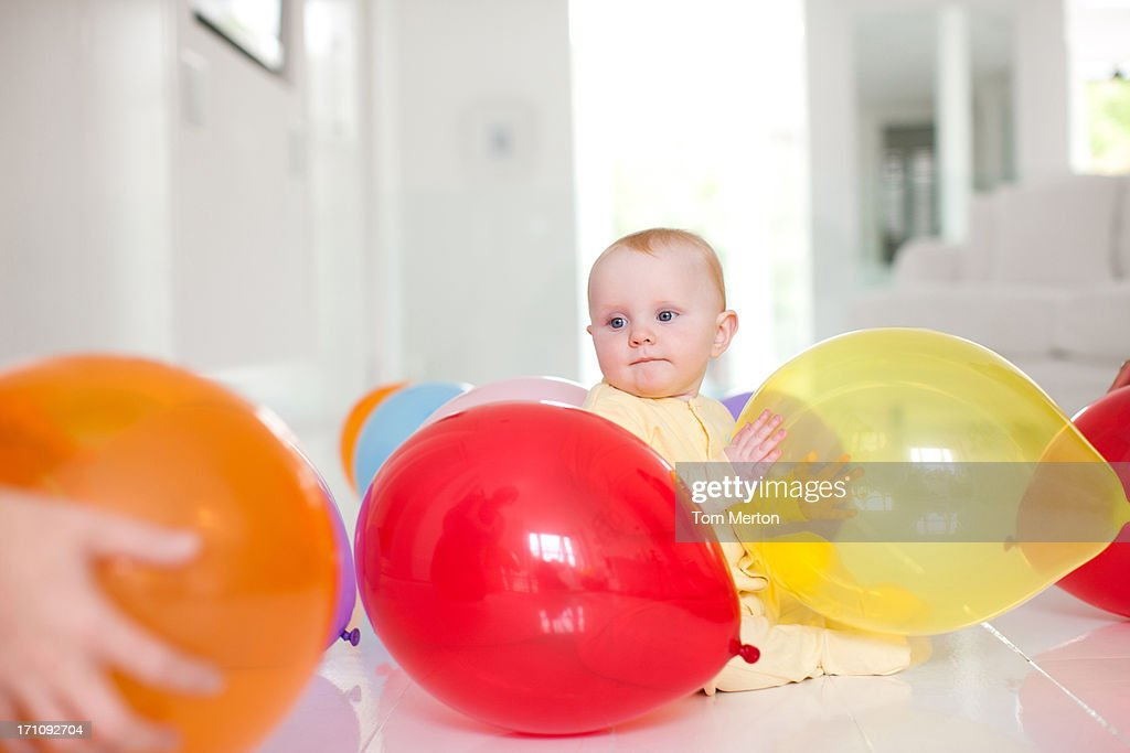 Curious baby with balloons : Stock Photo
