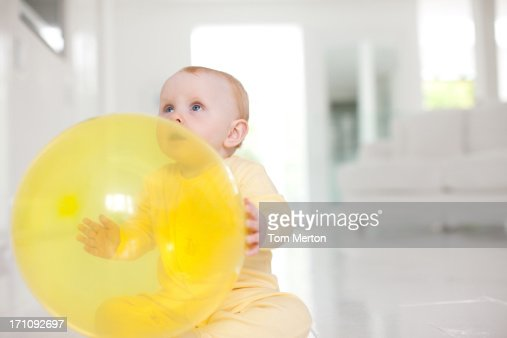 Curious baby with yellow balloon : Stock Photo