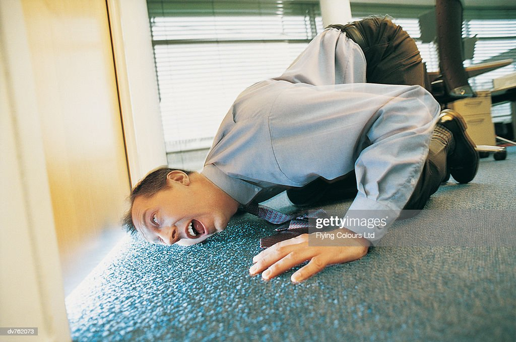 Curious Businessman Looking Under a Door in the Office : Stock Photo