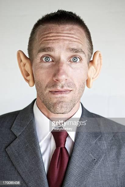Curieux Homme d'affaires est à la caméra avec de grandes oreilles
