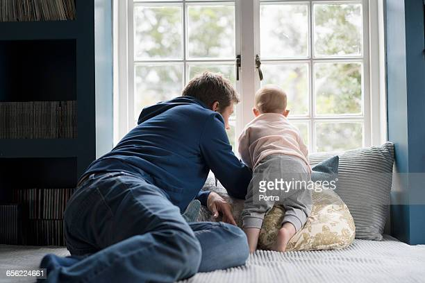 Curious father and son looking through window