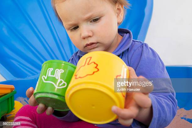 Curious female toddler playing with cups in garden
