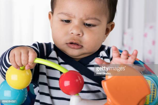 Curious Hispanic baby boy playing with toy