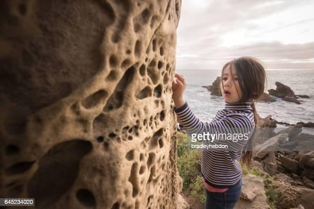 Curious little girl inspecting rock formations on beach cliffs