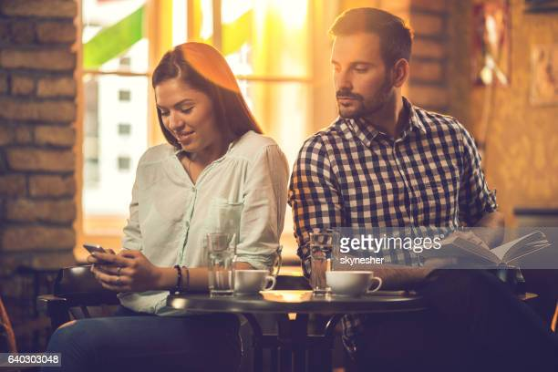 Curious man trying to see text message on girlfriend's phone.