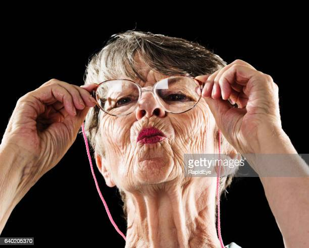 Curious old woman with pursed lips peers through spectacles