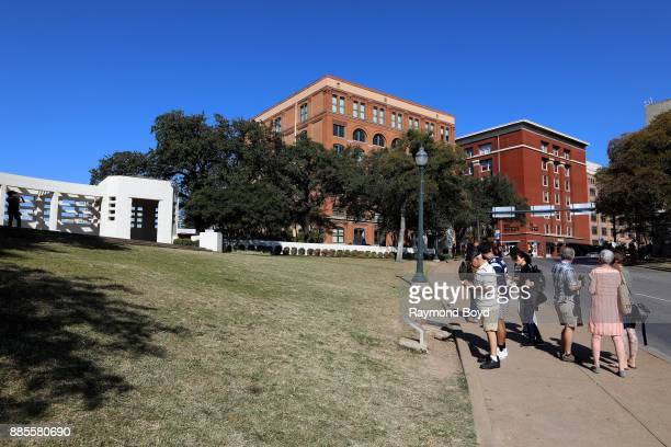 Curious onlookers gather along Elm Street at the site where President John F Kennedy was assassinated on November 22 1963 in Dallas Texas on November...