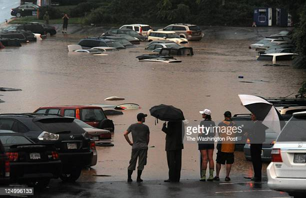 Curious residents drivers and those there to help drivers get home survey the scene where heavy rainfall Thursday flooded a commuter parking lot in...