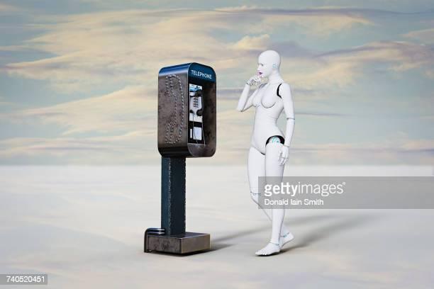 Curious robot woman examining pay telephone