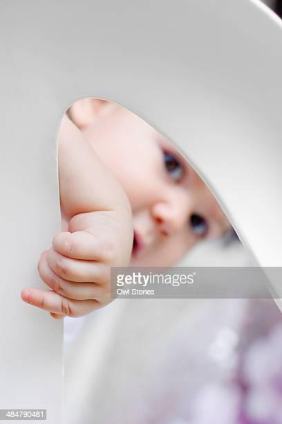 Curious toddler girl peeking through a hole