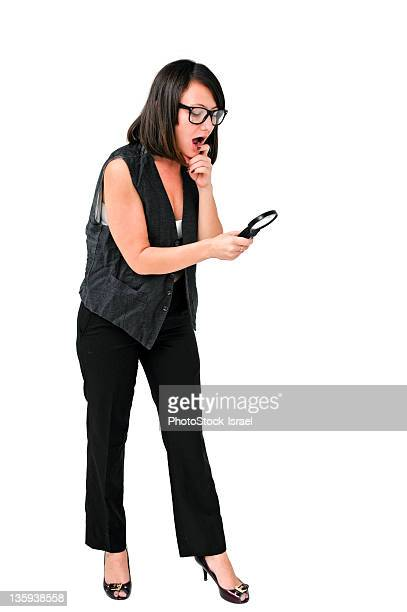 Curious woman looking through magnifying glass