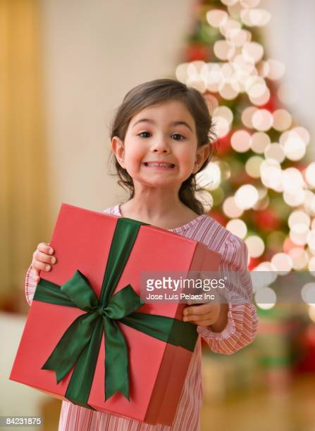 Curious young girl holding large Christmas gift