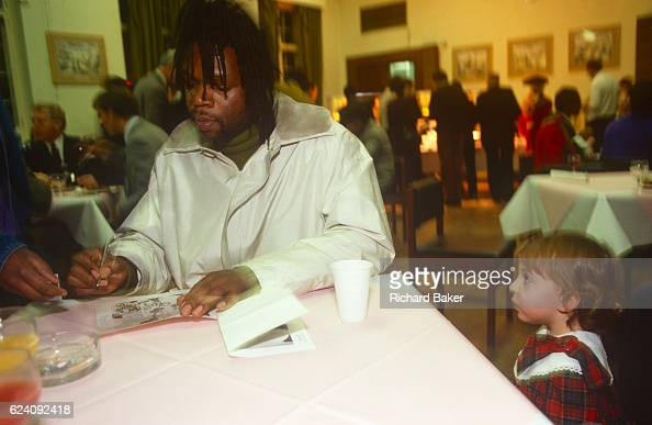 A curious young girl looks at the musician Jazzy B during a Mayor's Christmas lights event in Brixton town hall in December 1989 London England