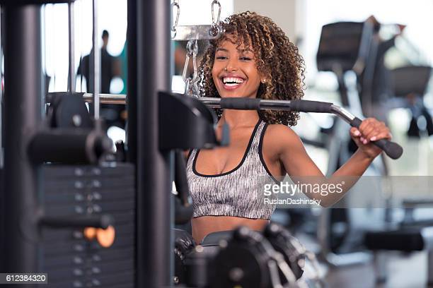Curled hair woman working out at GYM club.