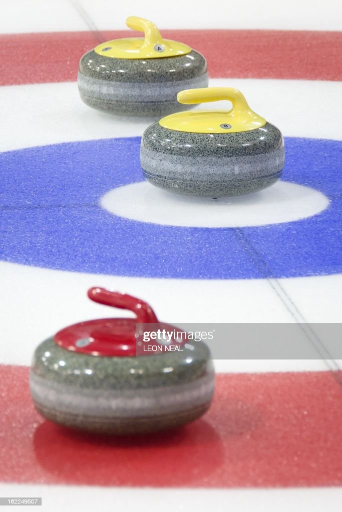 Curling stones are shown in play during a test event at the Olympic Curling Centre in Adler, Russia on February 21, 2013. With a year to go until the Sochi 2014 Winter Games, construction work continues as tests events and World Championship competitions are underway. AFP PHOTO / LEON NEAL