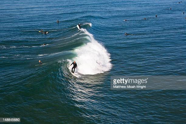 Curling wave and surfers from Huntington Beach Pier.
