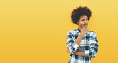 Thoughtful charming black teenage female in plaid shirt with curly afro hair on yellow background, reflective young biracial girl looking aside, with copy space for your advertising message