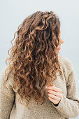 Curly brunette in a sweater on the coast holding hair with her hand