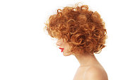 Profile portrait of young woman with beautiful red curly hair over wite background