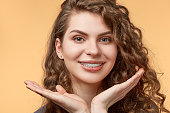 curly hair woman with brackets on biege background