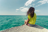 Relaxing teenage girl. Curly hair young woman is enjoing calm ocean water surface and clear sky and horizon at bahamas.