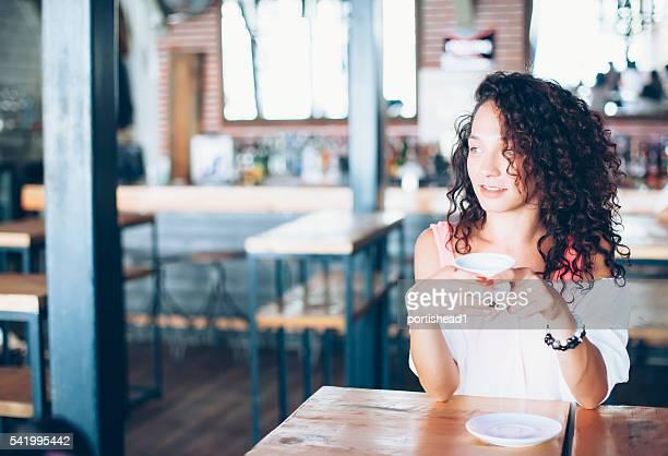 Ricci giovane donna bere il caffè in un bar