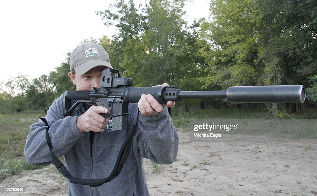 Curran Salter uses a semiautomatic rifle with a suppressor when hunting feral hogs to reduce noise and avoid spooking other hogs as he works to...