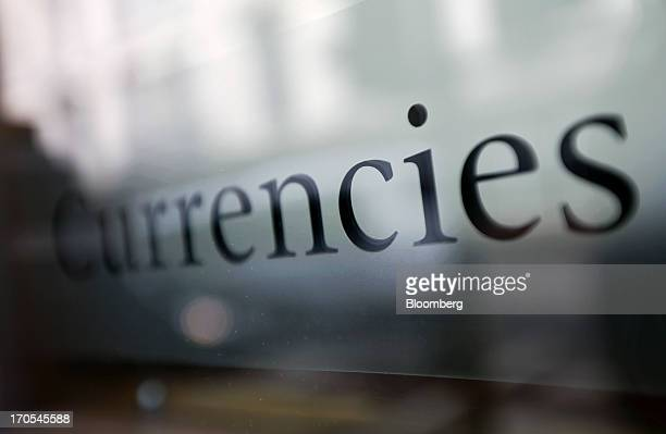 A 'Currencies' sign sits on the window of a private brokerage firm in London UK on Friday June 14 2013 Global regulators may start overseeing...