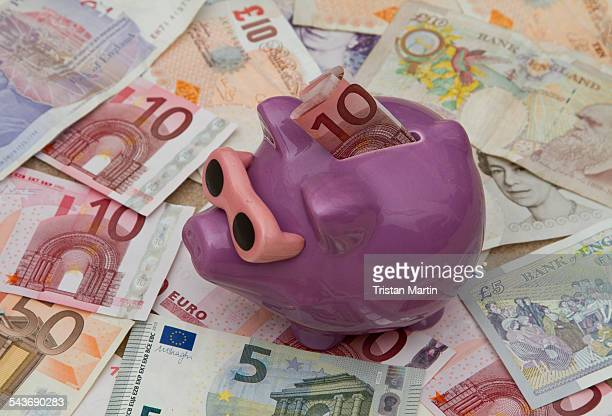 Currency A child's piggybank standing on a variety of British and European banknotes