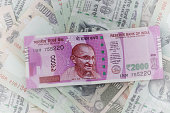 New 2000 Banknote (Indian Currency), laying  on 100 notes surface background.