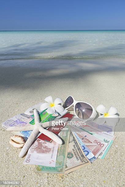 Currency, bank card, passport, sunglasses on beach
