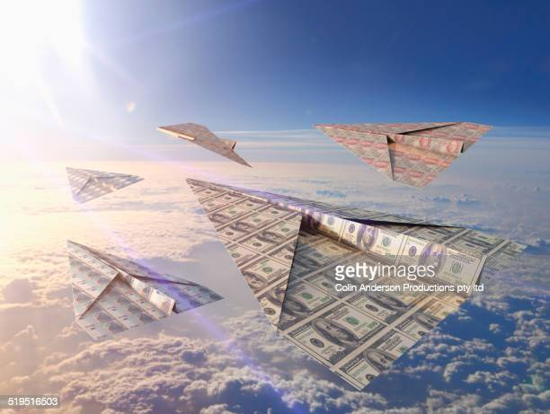 Currency bills folded into paper airplanes in atmosphere