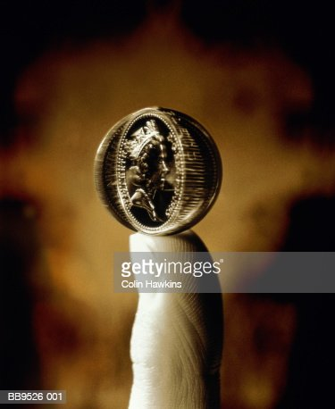 UK currency: coin spinning on fingertip (Digital Composite) : Stock Photo