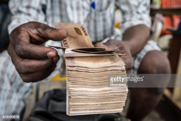 A currency dealer counts a bundle of naira banknotes for exchange on the 'black market' in Lagos Nigeria on Wednesday July 26 2017 Nigeria's economy...