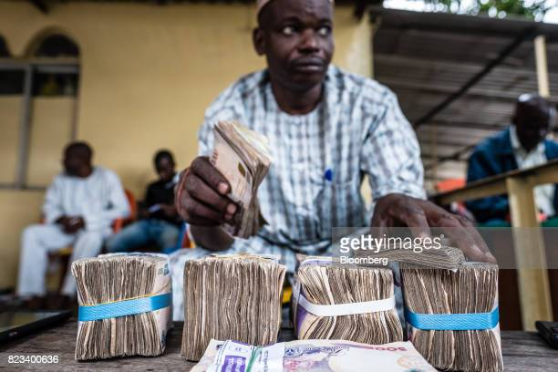 A currency dealer counts bundles of naira banknotes for exchange on the 'black market' in Lagos Nigeria on Wednesday July 26 2017 Nigeria's economy...