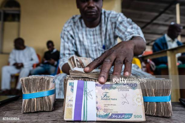 A currency dealer handles bundles of naira banknotes for exchange on the 'black market' in Lagos Nigeria on Wednesday July 26 2017 Nigeria's economy...