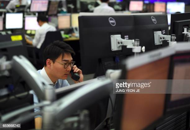 A currency dealer monitors exchange rates in a trading room at the KEB Hana Bank in Seoul on March 16 2017 South Korean shares rose 08 percent on...