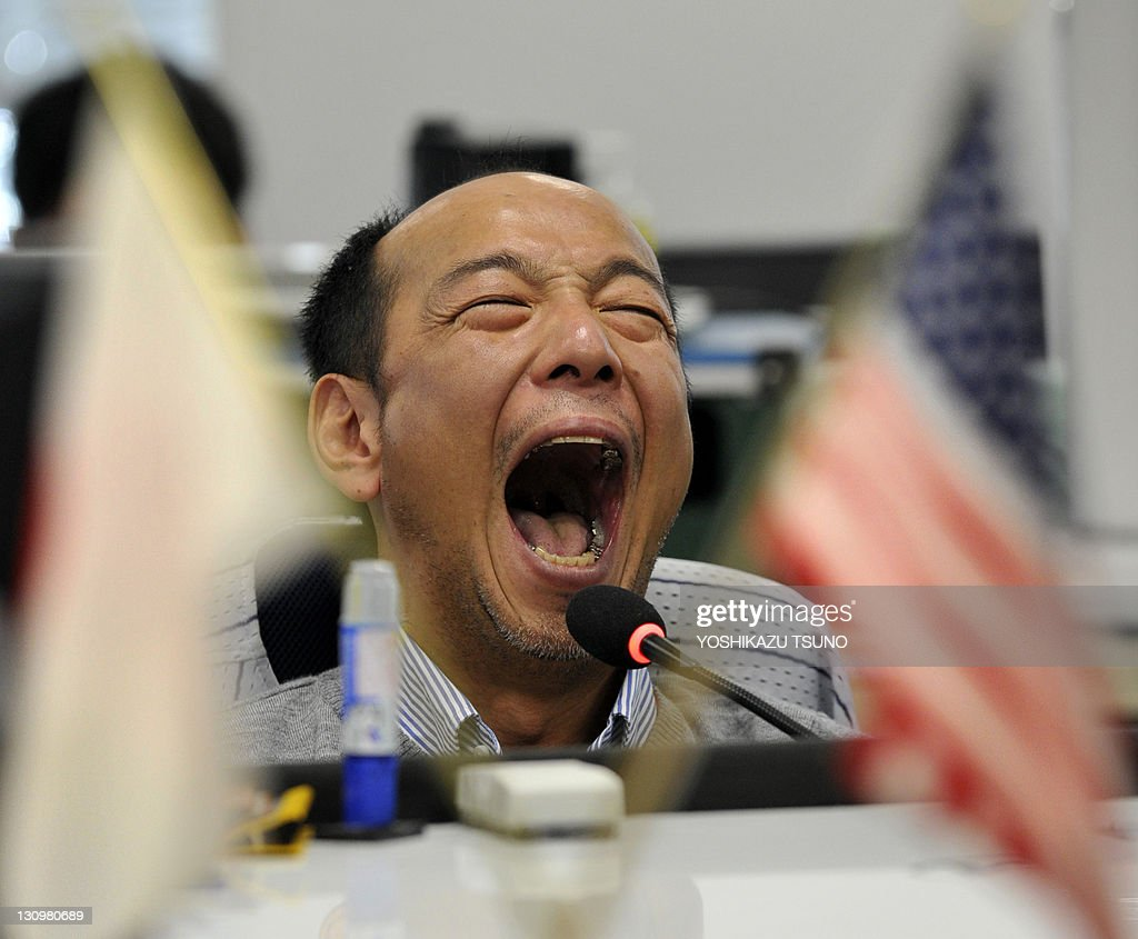 A currency dealer opens his mouth at a foreign exchange market in Tokyo on October 31, 2011. Japan intervened in currency markets for the first time since August to weaken the yen. The US dollar climbed to 78.95 yen at around after hitting a fresh post-war low of 75.32 yen in Oceanian trade earlier. AFP PHOTO / Yoshikazu TSUNO