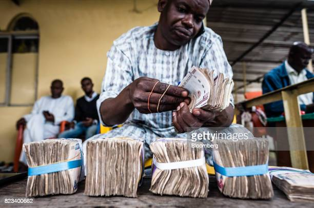 A currency dealer uses a mobile phone as he counts bundles of naira banknotes for exchange on the 'black market' in Lagos Nigeria on Wednesday July...