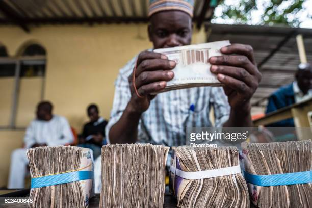A currency dealer uses an elastic band to bundle naira banknotes for exchange on the 'black market' in Lagos Nigeria on Wednesday July 26 2017...