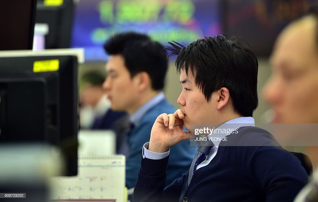Currency dealers monitor exchange rates in front of screens showing ...
