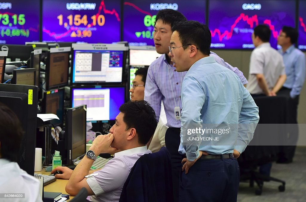 Currency dealers monitor exchange rates in a trading room at the KEB ...
