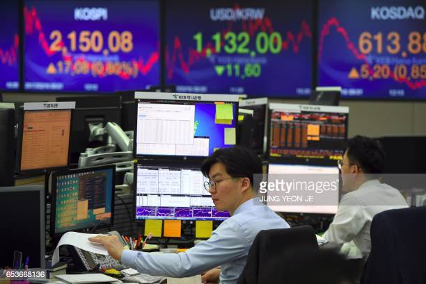 Currency dealers monitor exchange rates in a trading room at the KEB Hana Bank in Seoul on March 16 2017 South Korean shares rose 08 percent on March...