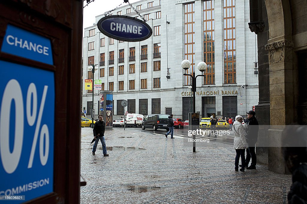 A currency exchange stands opposite the Czech central bank, center, in Prague, Czech Republic, on Tuesday, Jan. 8, 2013. The Czech economy is showing weak domestic demand as households and businesses cut spending due to government austerity programs and the euro area's debt crisis. Photographer: Bartek Sadowski/Bloomberg via Getty Images
