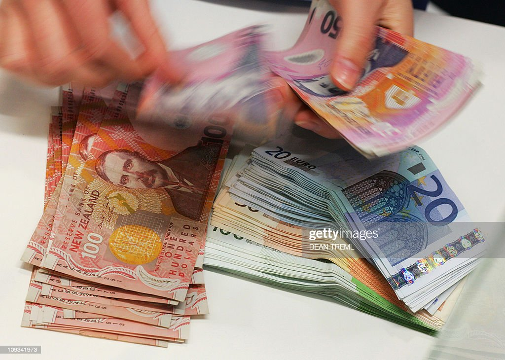 A currency exchange teller counts out New Zealand dollars alongside a stack of Euros in Auckland 21 April 2007 The New Zealand dollar hit 7491 US...