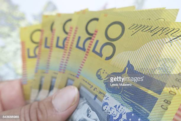 Currency Female hand holding lots of Australian $50 notes