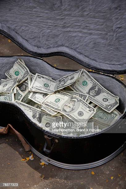 Currency in busker's guitar case