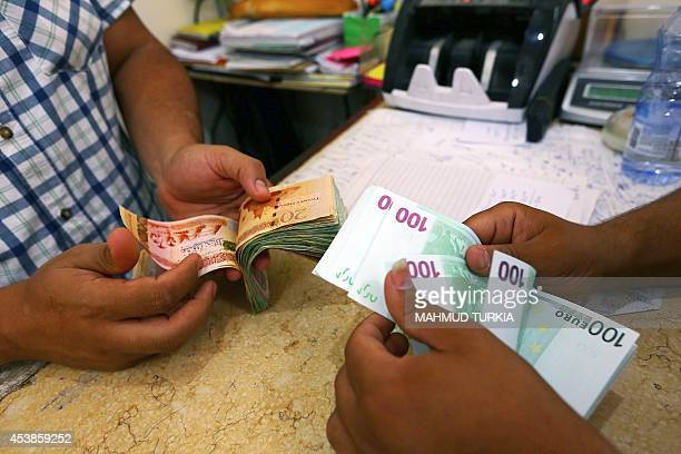 Currency is changed at a currency exchange in the Souk ilJumaa district in the center of the Libyan capital Tripoli on August 20 2014 Regular thuds...