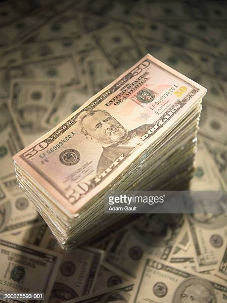 US Currency: Stack of fifty dollar bills on scattered bills, close-up